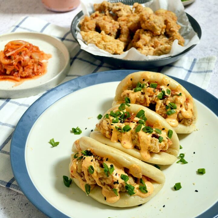 steamed bao buns with fried tender chickens kimchi mayonnaise and green onion