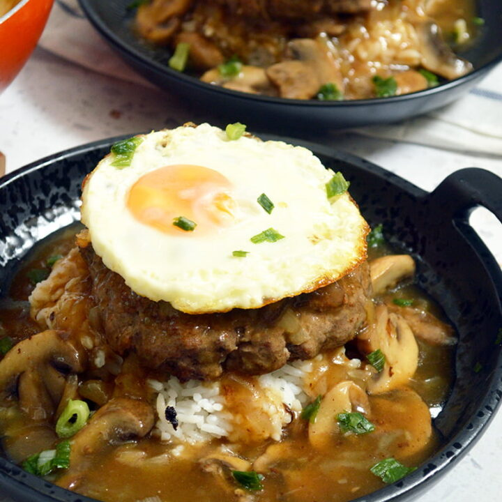 a bowl of rice topped with a beef patty and a sunny side up egg, smothered with mushroom gravy